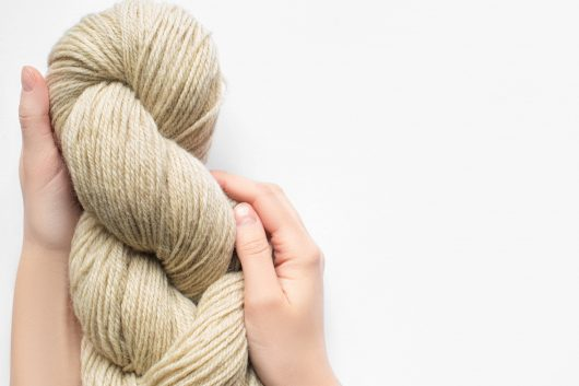 cropped view of woman holding beige yarn on white background with copy space