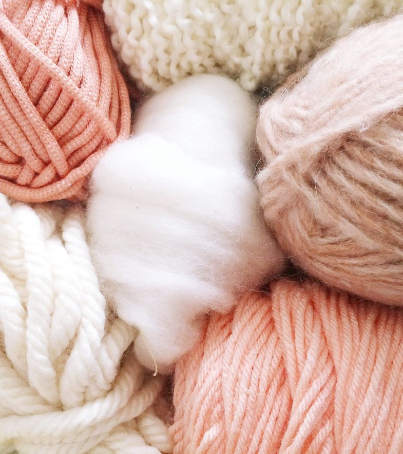 Just peachy! Full frame shot of pastel-colored skeins of yarn.